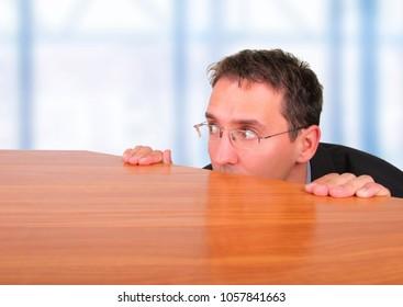 Business man hide behind desk in office