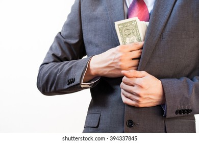 Business man hiding money in jacket pocket - Corruption and Fraud Concept
