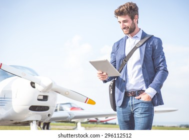 business man with his airplanes. He is walking in the airport with the tablet checking the schedule.
