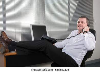 Business man at his computer with customer in phone