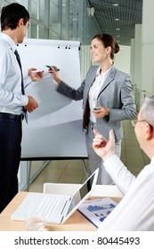 A business man and his partner standing by whiteboard and interacting