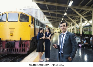 Business man hold mobile stand at railway with couple women and yellow train in background.