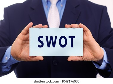 Business man hold paper SWOT text on it
