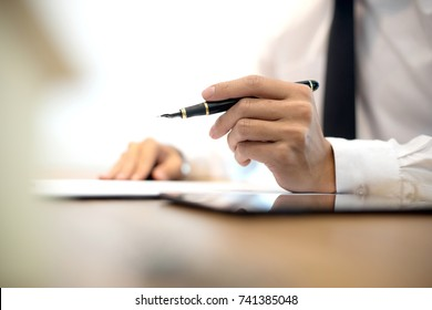 Business man hold pen on the air white mode blur background more copyspace