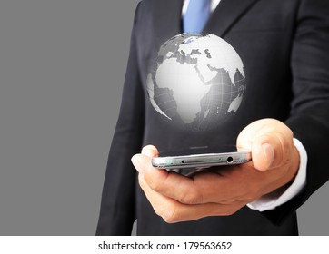 Business man hold smart phone with glowing digital wire globe