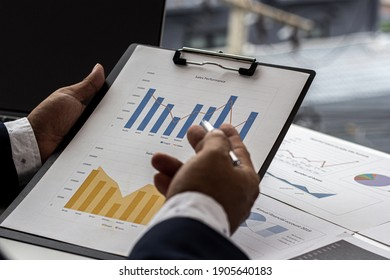A business man holding a bar chart document used to accompany the company's monthly meeting, Businessman discussing the company's annual sales report to the attendees.