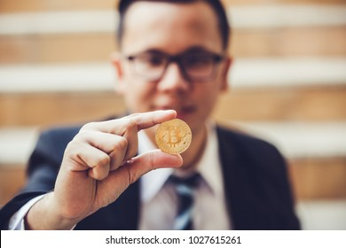 business man holding bitcoin on hand. Focus on bitcoin