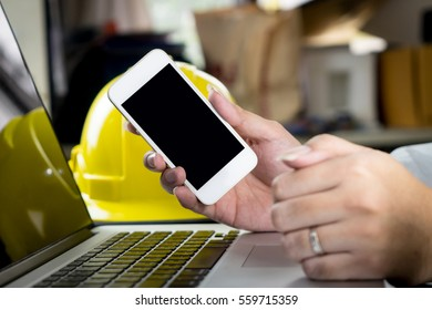 business man is holding Blank Smartphone screen On engineering working desk for application mock up template.