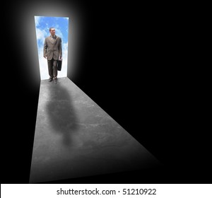 A business man is holding a briefcase and standing at an open door with light behind him. The room is dark and black. Can represent opportunity, fear, risk or success.