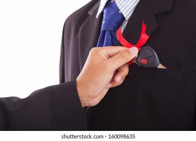 Business man holding a car key.