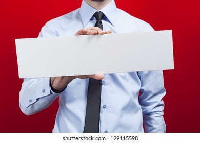 Business man holding card against red background.
