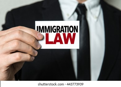Business man holding a card with the text: Immigration Law