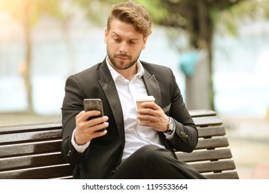 Business man holding a coffee and smartphone in the park