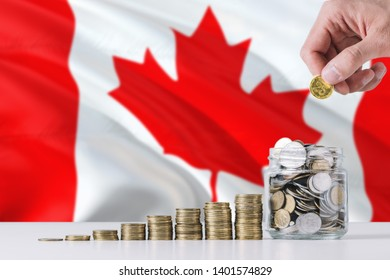 Business man holding coins putting in glass, Canada flag waving in the background. Finance and business concept. Saving money.