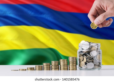Business man holding coins putting in glass, Mauritius flag waving in the background. Finance and business concept. Saving money.