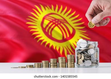 Business man holding coins putting in glass, Kyrgyzstan flag waving in the background. Finance and business concept. Saving money.