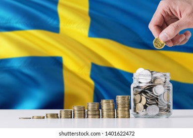 Business man holding coins putting in glass, Sweden flag waving in the background. Finance and business concept. Saving money.