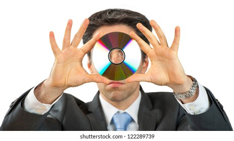 Business Man is holding a Data CD in front of his face.