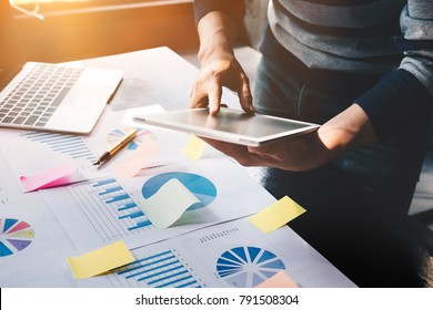 business man holding  digital tablet and use laptop to working document accountant analyze income & budget & tax is are planning a marketing plan to improve the quality of their sales in the future.