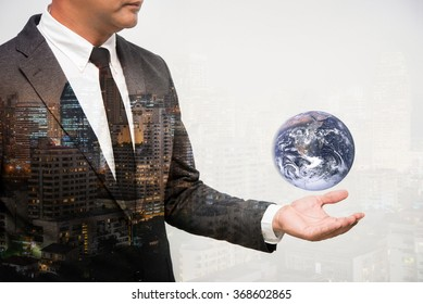 Business Man Holding Earth globe double exposure with building. Elements of this image furnished by NASA