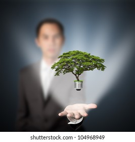 business man holding green energy concept light bulb in hand