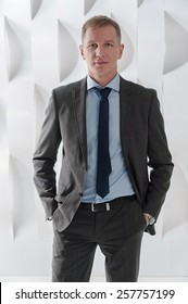 Business man holding hands in pockets on background of abstract modern urban interior