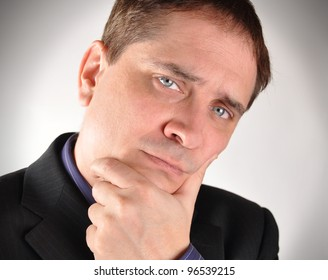 A business man is holding his hand to his face and thinking. Use it for a financial investment or challenge concept.