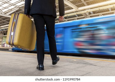 Business man holding his handbag and walking in sky train station.