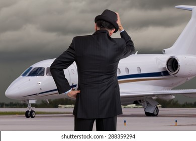 Business man holding his head in front of private airplane