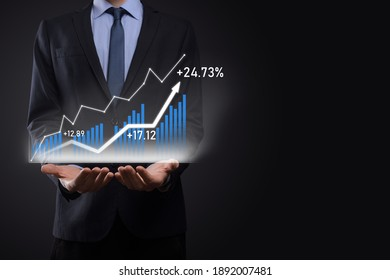 Business man holding holographic graphs and stock market statistics gain profits. Concept of growth planning and business strategy. Display of good economy form digital screen