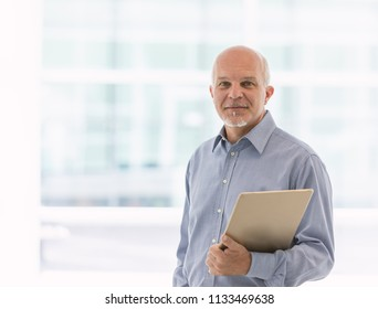 Business man holding laptop in one arm while facing the camera.