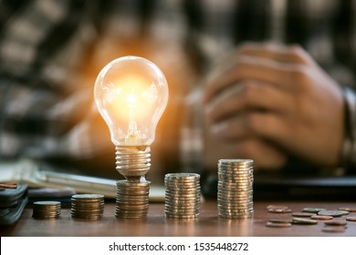 Business man holding light bulb on the Green background nature and writing on note book it for financial