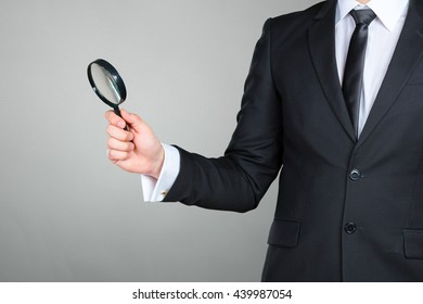 business man holding magnifying glass concept