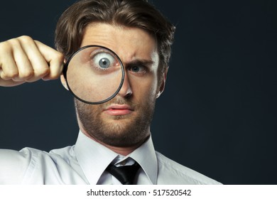 business man holding magnifying glass