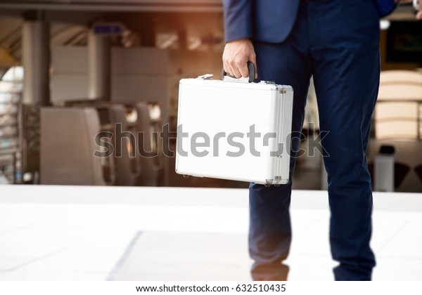 Business man is holding metallic brief case at station