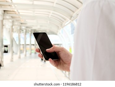 Business man holding mobile about to call customer. manager using mobile phone. blank phone screen. Blurred background. Business financial saleman concept.