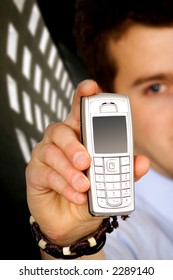 business man holding a mobile phone over a dark background
