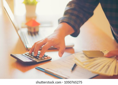 Business man holding money buy house business and laptop computer