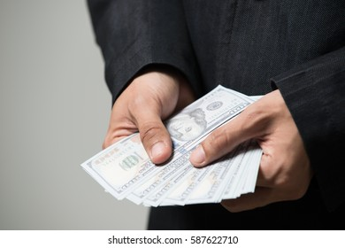 Business man holding money on white background ,Photography in the studio in the corruption concept.