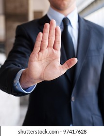 Business man holding out hand, indicating stop