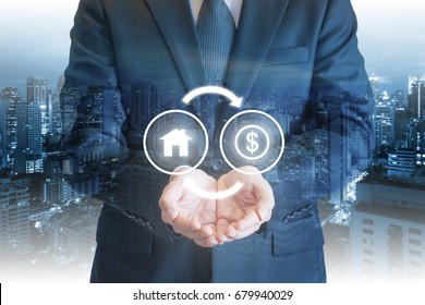 Business man holding out hands under house and money exchanging icons with cityscape background for mortgage, home loan, residential purchasing and housing payment concept