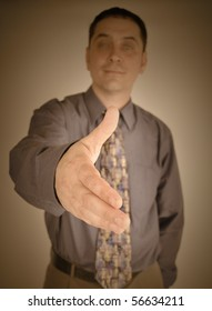 A business man is holding out his hand ready to shake a person's hand for a meeting, negotiation or finance deal. Can represent a partnership or job interview.