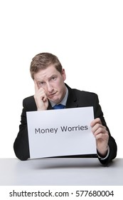 business man holding a paper sign with the words money worries written on it looking unhappy
