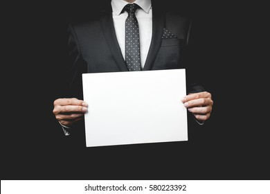 A business man holding a paper. Studio shot
