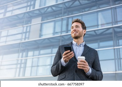 Business man holding phone drinking coffee at bank office thinking of the future. Aspirational businessman dreaming of career hope.