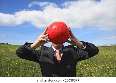 A business man holding a red ball hiding his face