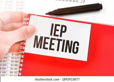 Business man holding a red notebook and white card with text IEP MEETING. Financial concept