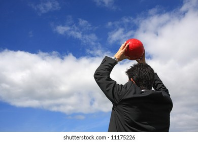 A business man holding a red soccer ball