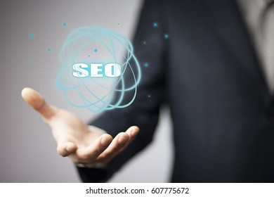Business man holding SEO text on screen