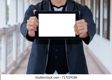 Business man holding and shows touch screen tablet pc